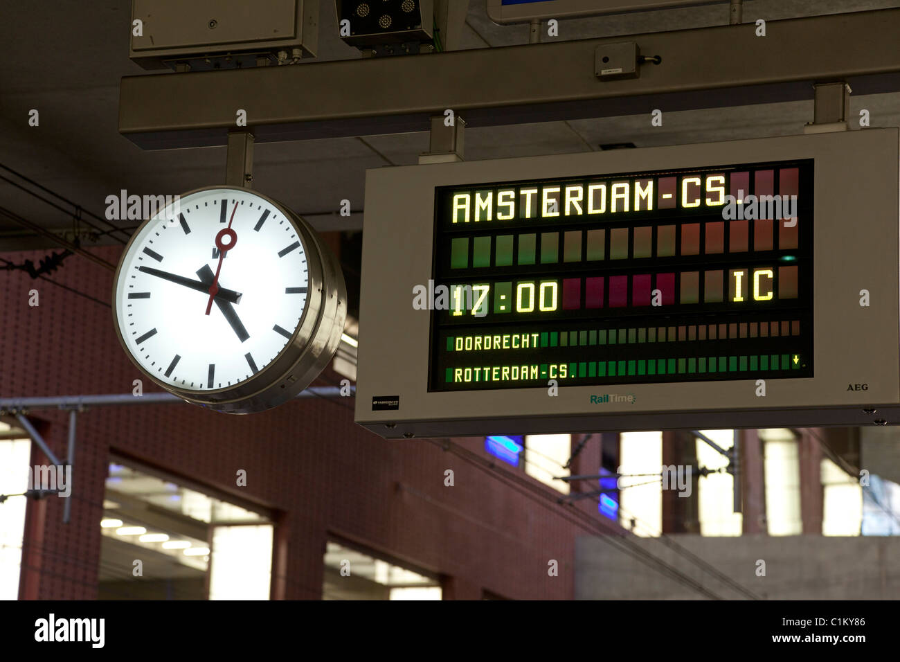 Station sign to Amsterdam with clock - Stock Image