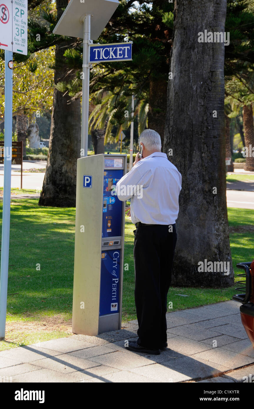 A motorist feeds a parking meter in a street, Perth,Western Australia - Stock Image