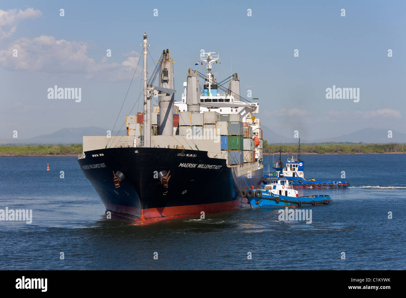Container ship with two tugs arriving at the Port of Corinto, Nicaragua - Stock Image