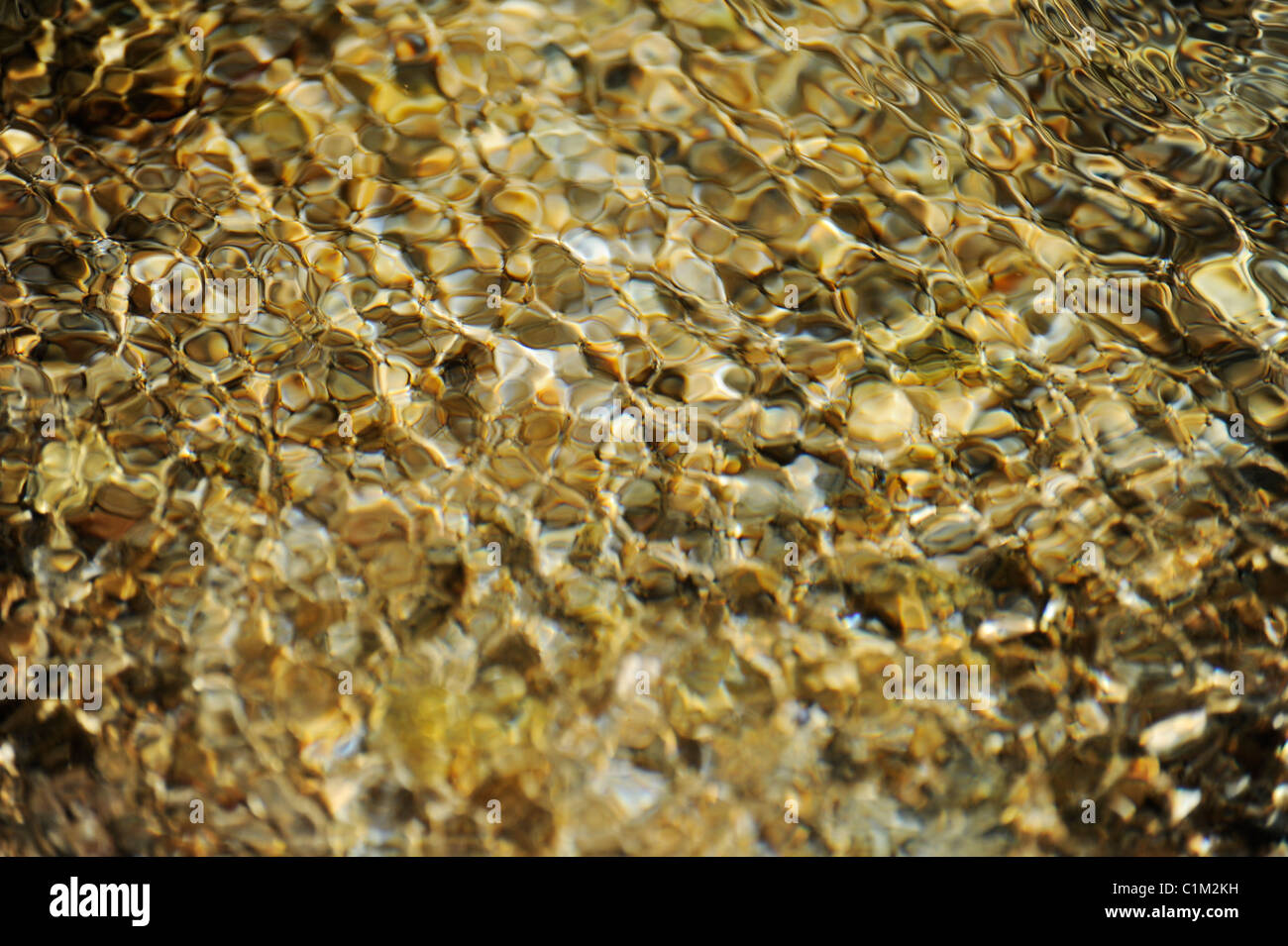 Close-up of water rippling over pebbles in a shallow part of river. - Stock Image