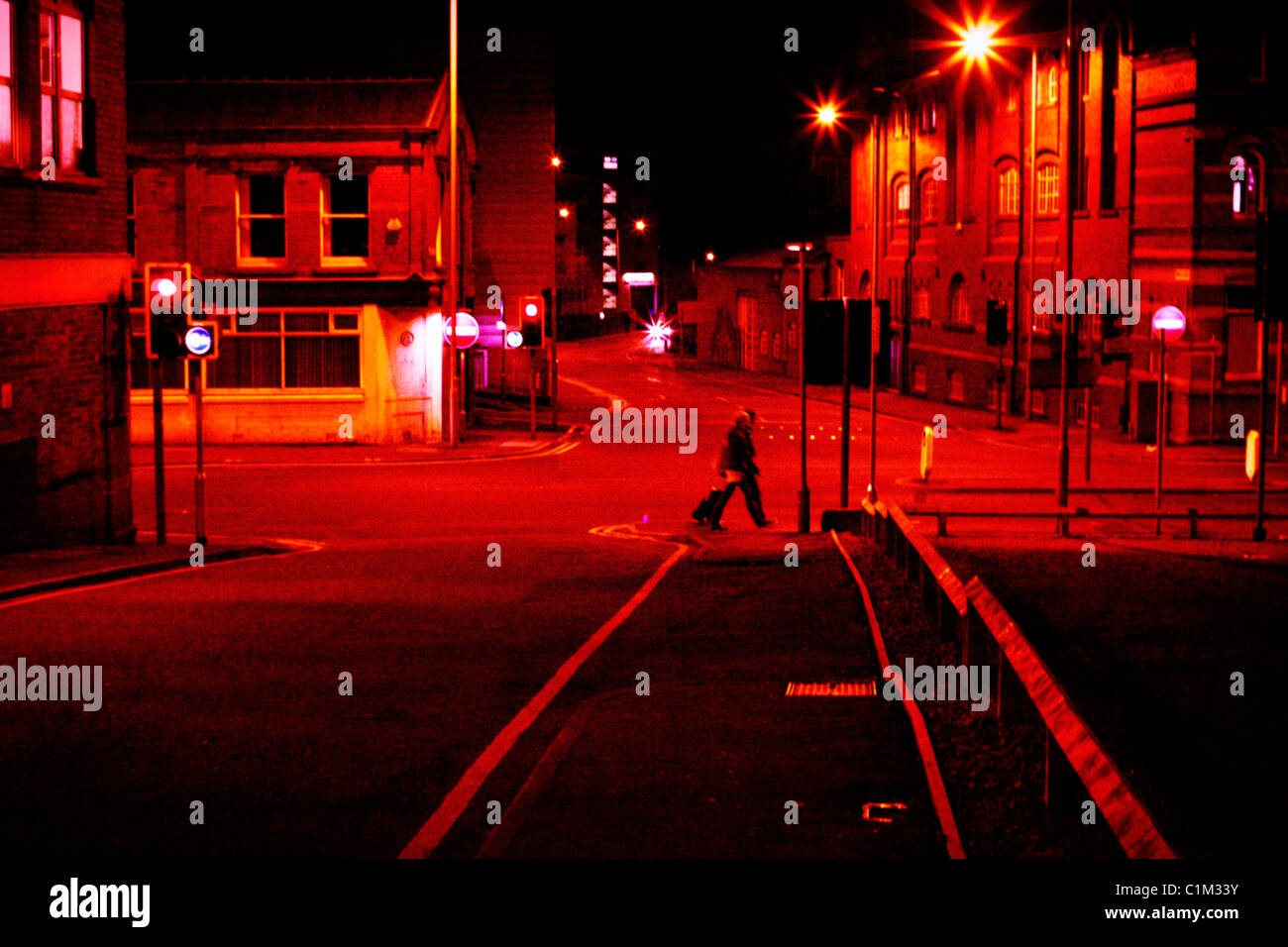 Two women walking alone at night in city - Stock Image
