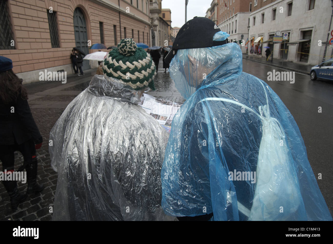 Two elderly lost wet tourists in plastic rain ponchos get wet as they try to read a map in Rome, Italy, Europe - Stock Image