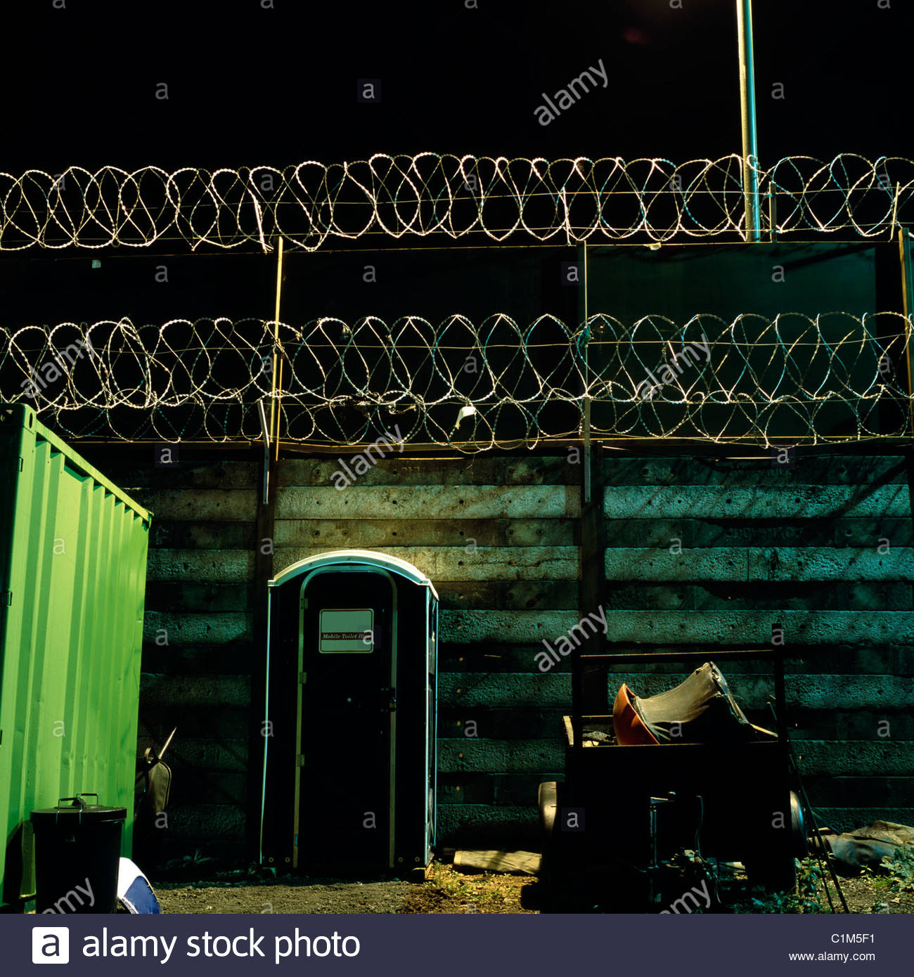 Security fencing and portaloo at yard in the night, Gloucestershire, UK. - Stock Image