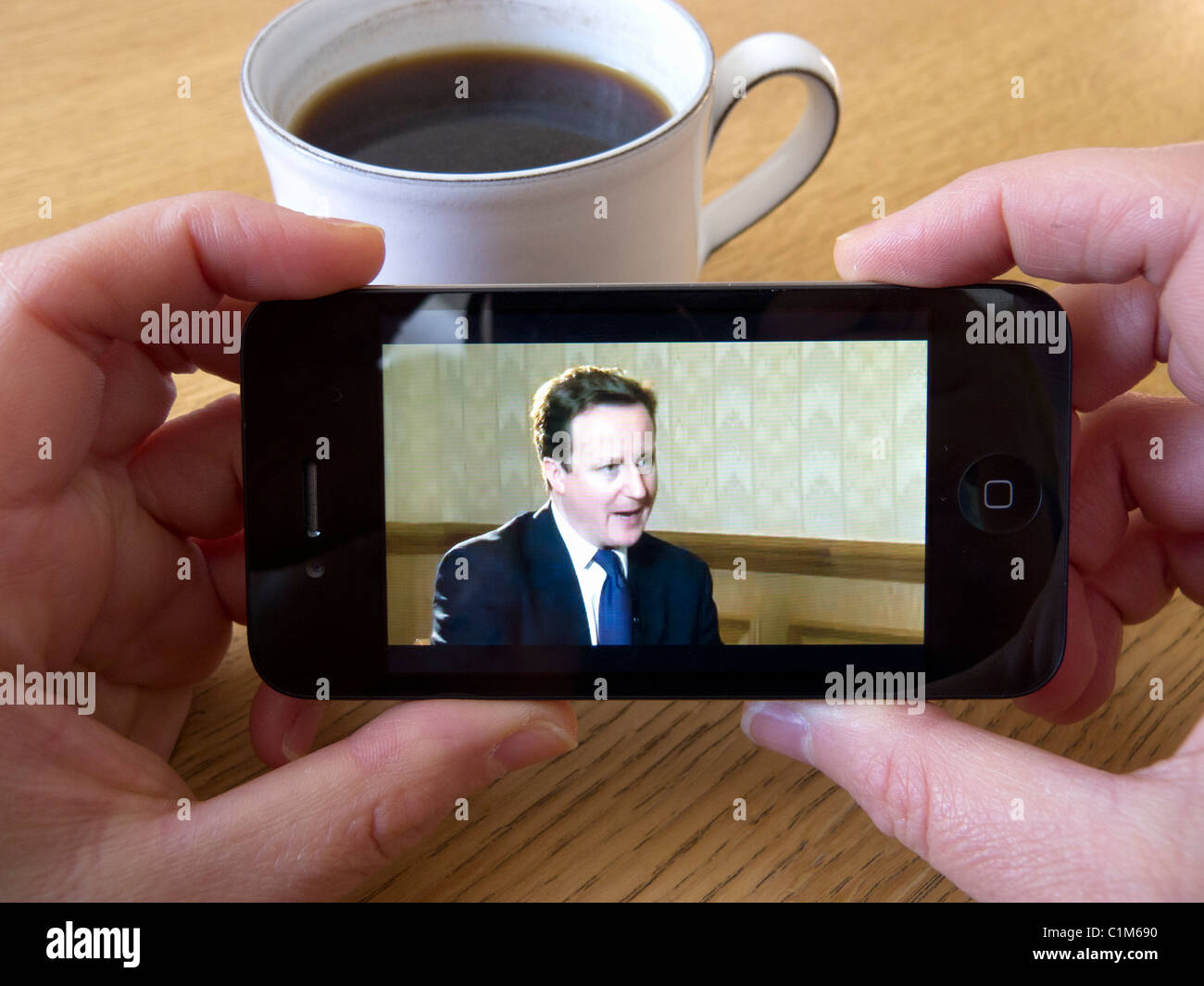 Watching video news of British Prime Minister David Cameron via Youtube on an Apple iphone 4G smart phone - Stock Image