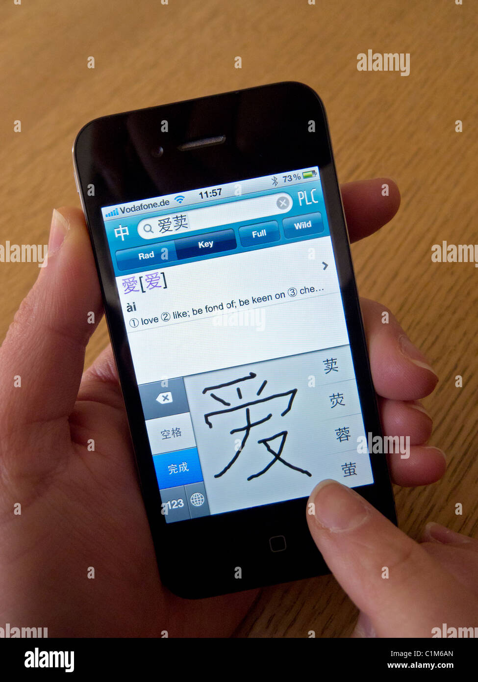 Student using app to learn mandarin Chinese characters on an Apple iphone 4G smart phone - Stock Image