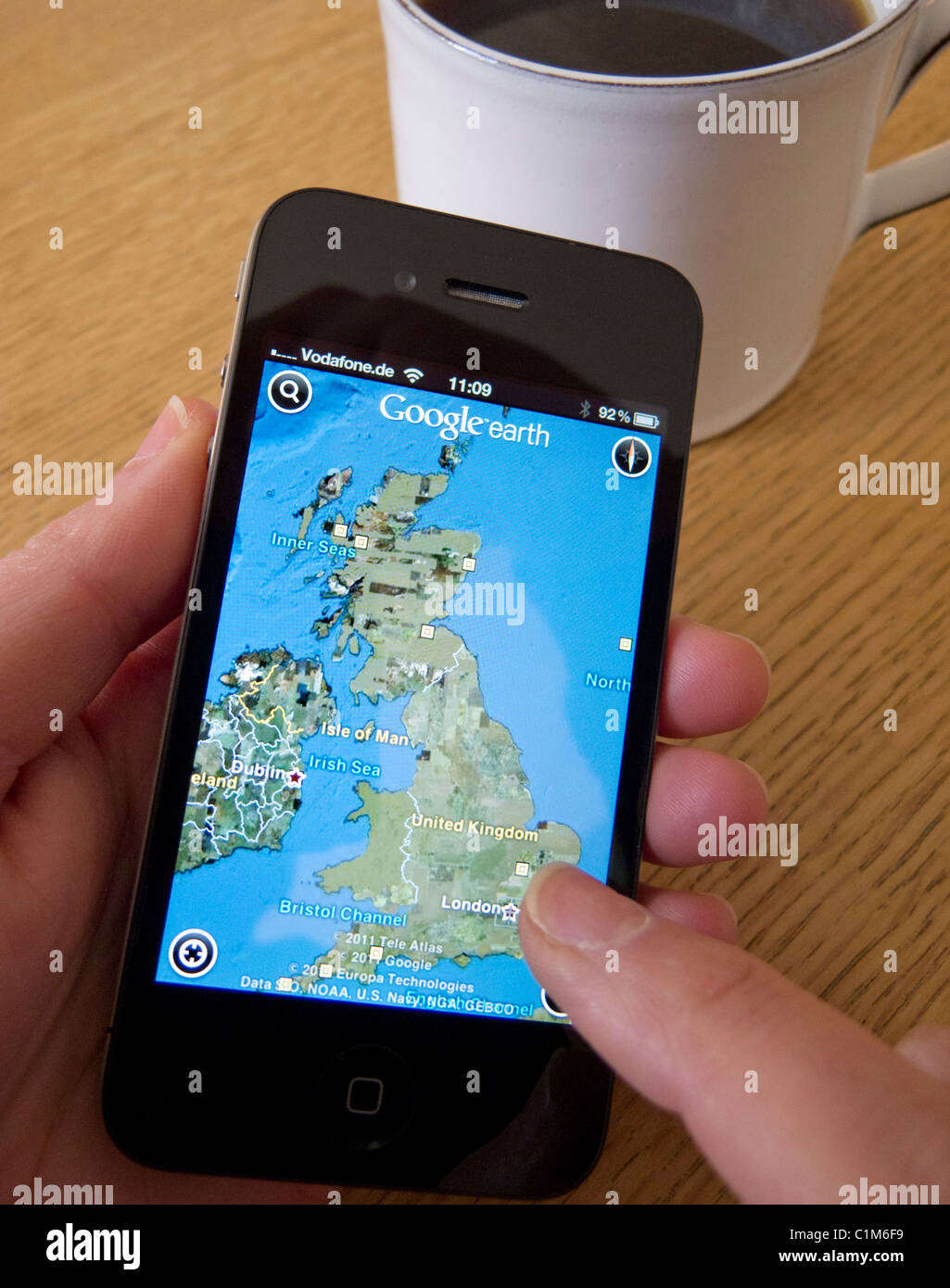 Using Google Earth satellite map on an Apple iphone 4G smart phone - Stock Image