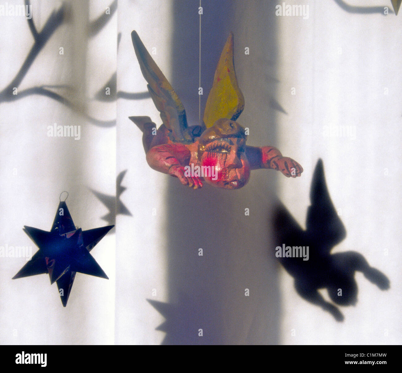 A pudgy, flying angel Christmas ornament casts his shadow in an art gallery window, in downtown Mountainair, New - Stock Image