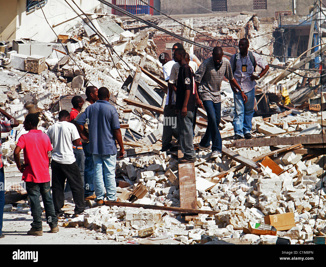 People walking through the ruins of Port au Prince after the Haiti earthquake - Stock Image