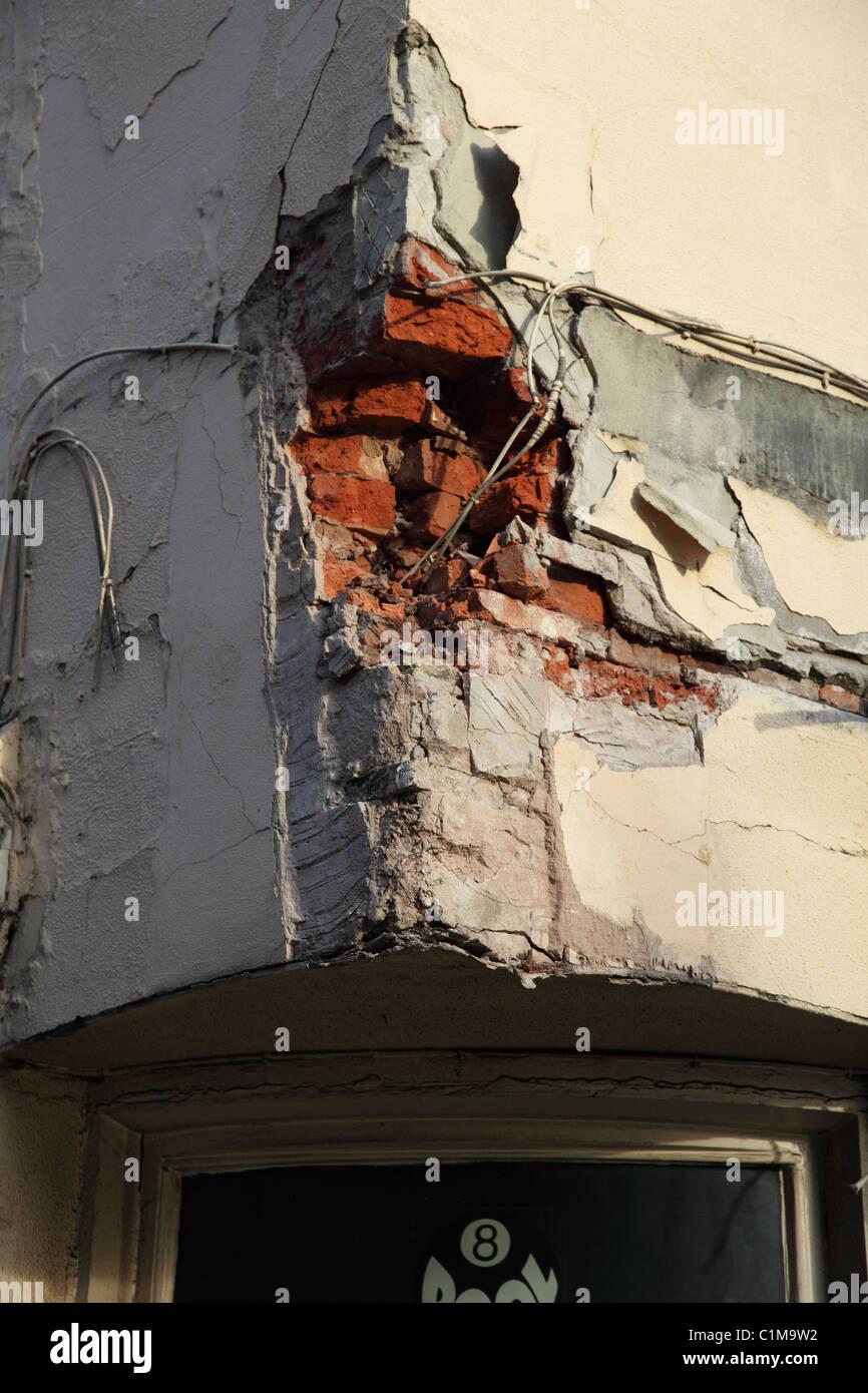 Damaged brickwork on a building in a U.K. city. - Stock Image