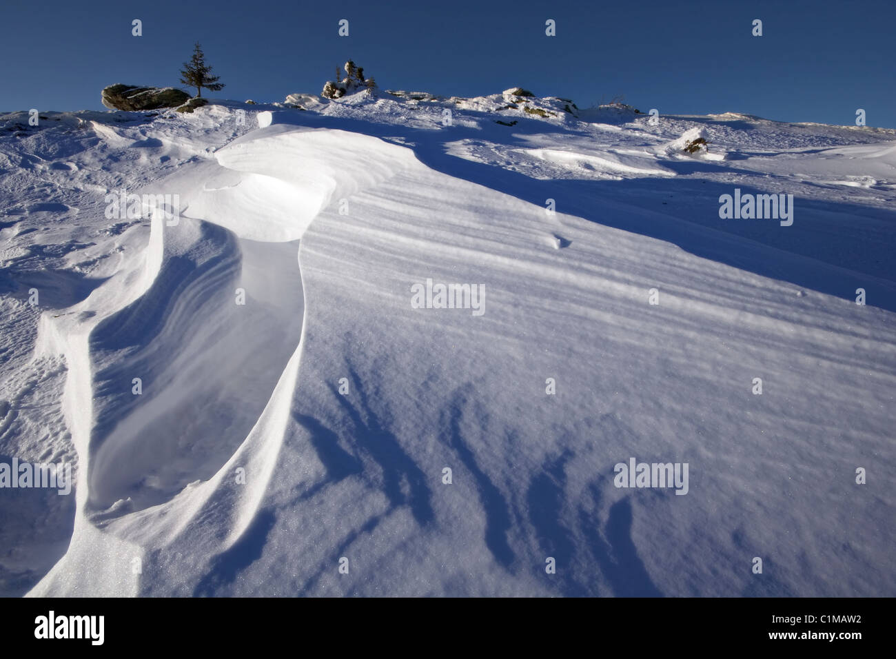 Snowdrift with wavy snow shapes. Winter landscape. National park Taganay. South Ural mountains. Russia. - Stock Image