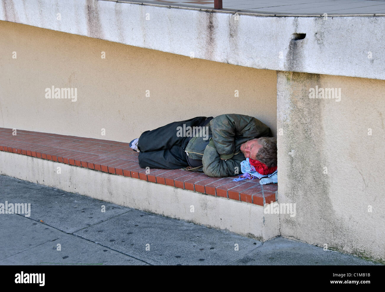 A homeless man sleeping by a local church. - Stock Image