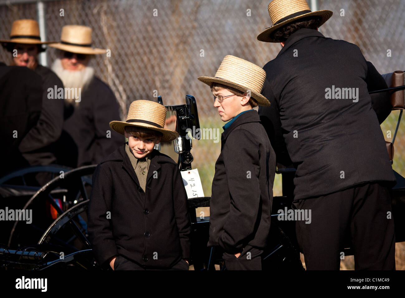 Amish boys watch a horse buggy auction at the annual Mud Sale in Gordonville, PA Stock Photo