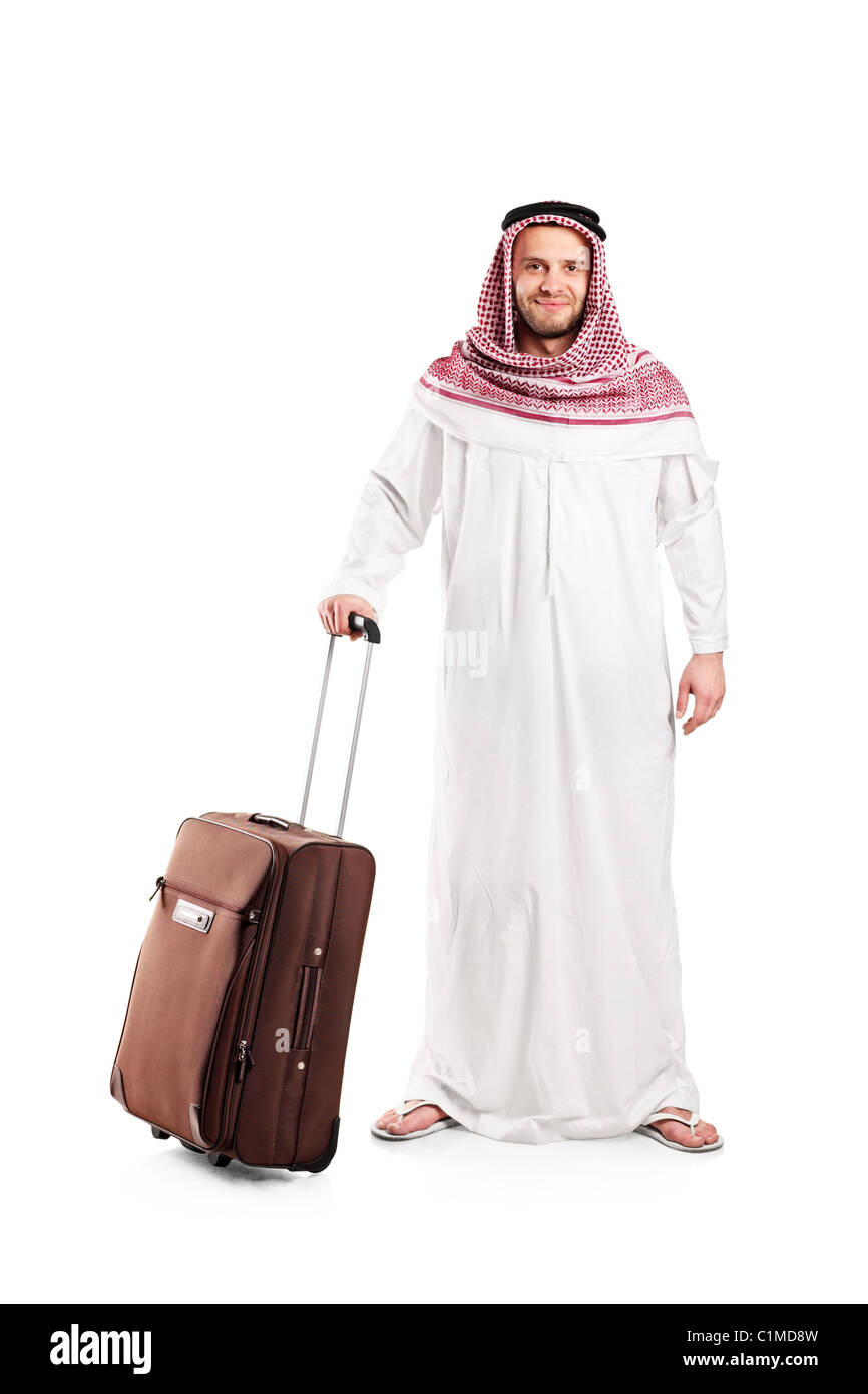 Full length portrait of an Arab tourist carrying a suitcase - Stock Image