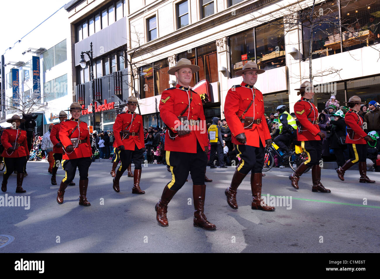 Canadian Mounties marching on Ste Catherine street in Montreal during the St Patrick's Day parade. - Stock Image