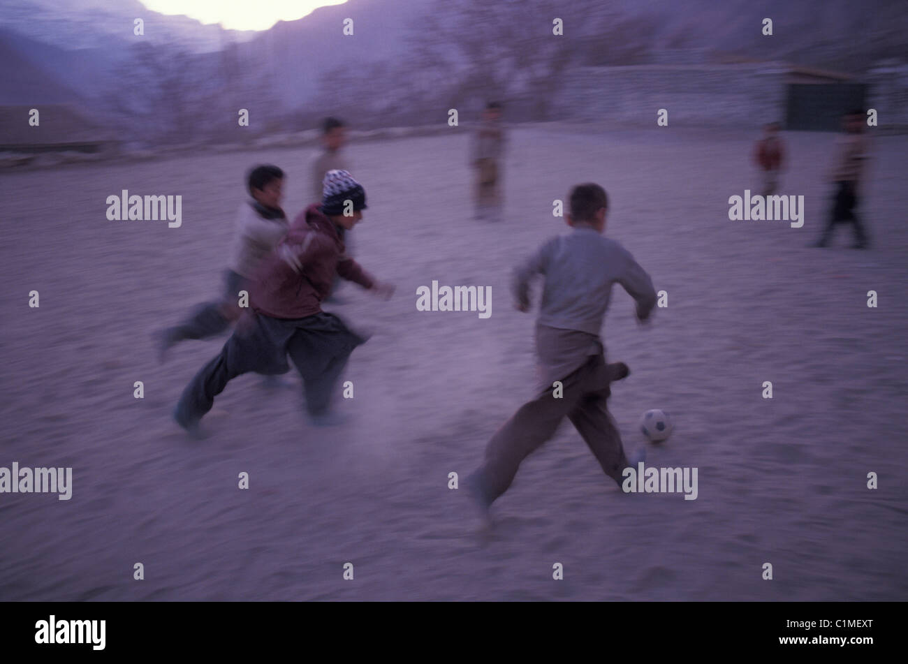 schoolboys in dusty school yard play soccer in Karimabad Hunza region of Pakistan - Stock Image