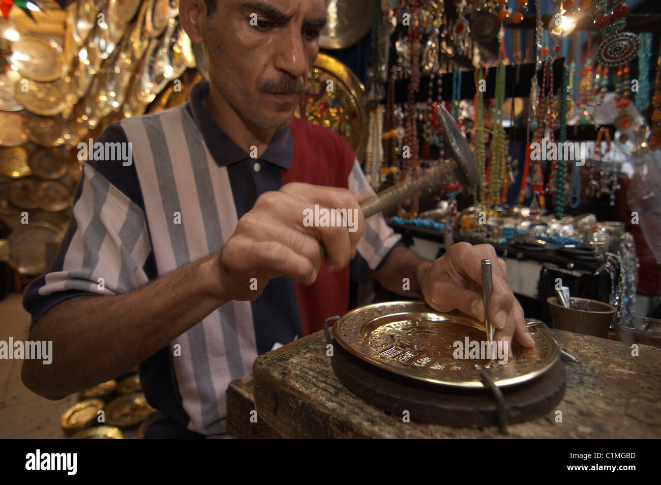 Tunisia - Tunis a shop seller make a brass plate in the medina - Stock Image