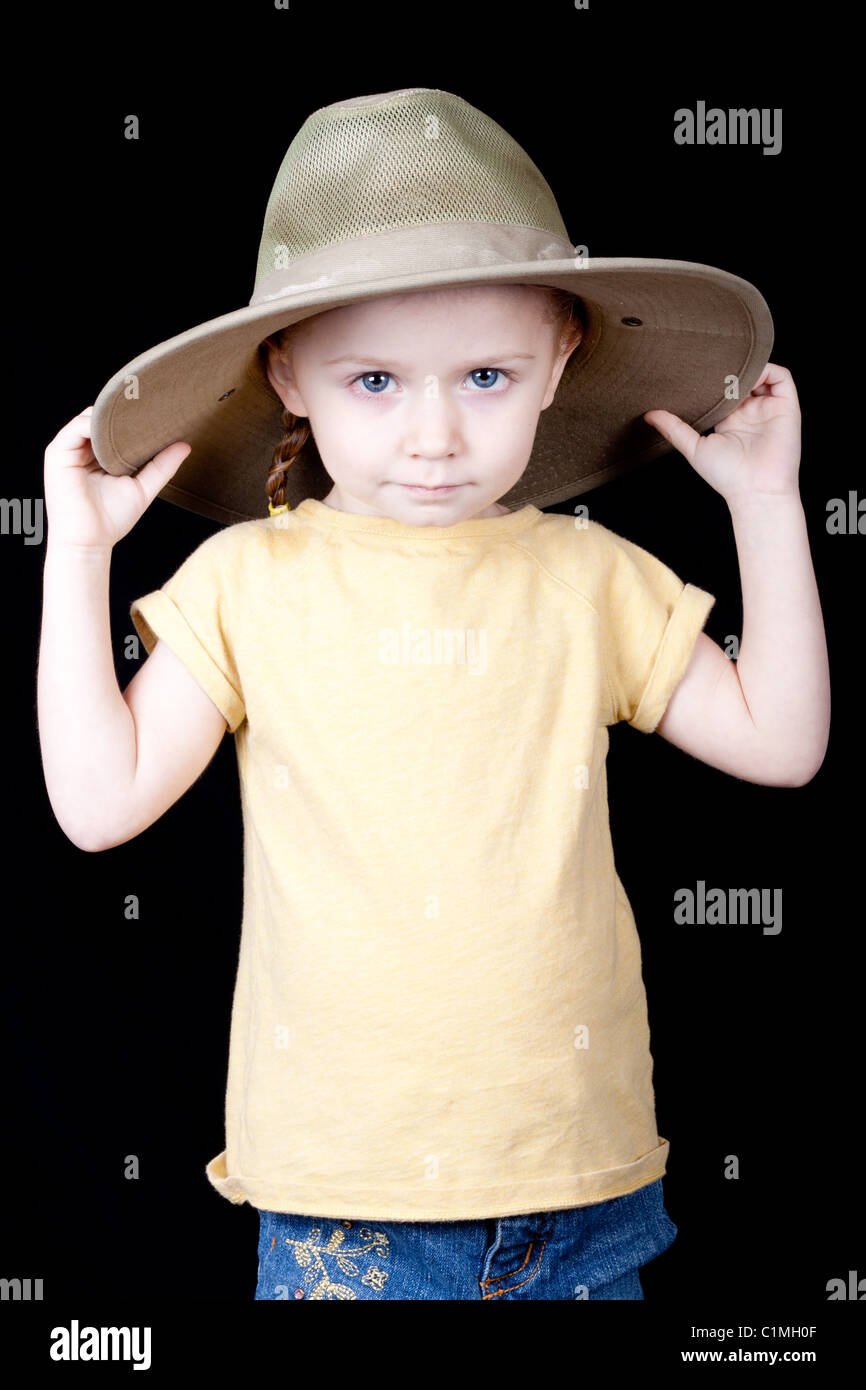 f811a88af9914 A young girl with a jungle style safari hat on. Her hands are on the hat  and she is pulling it down.