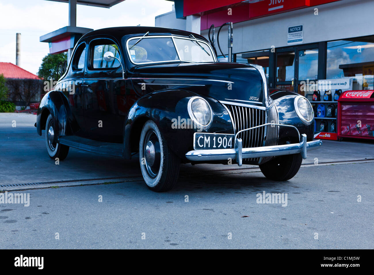 A Ford coupe at a service station in Canterbury, New Zealand - Stock Image