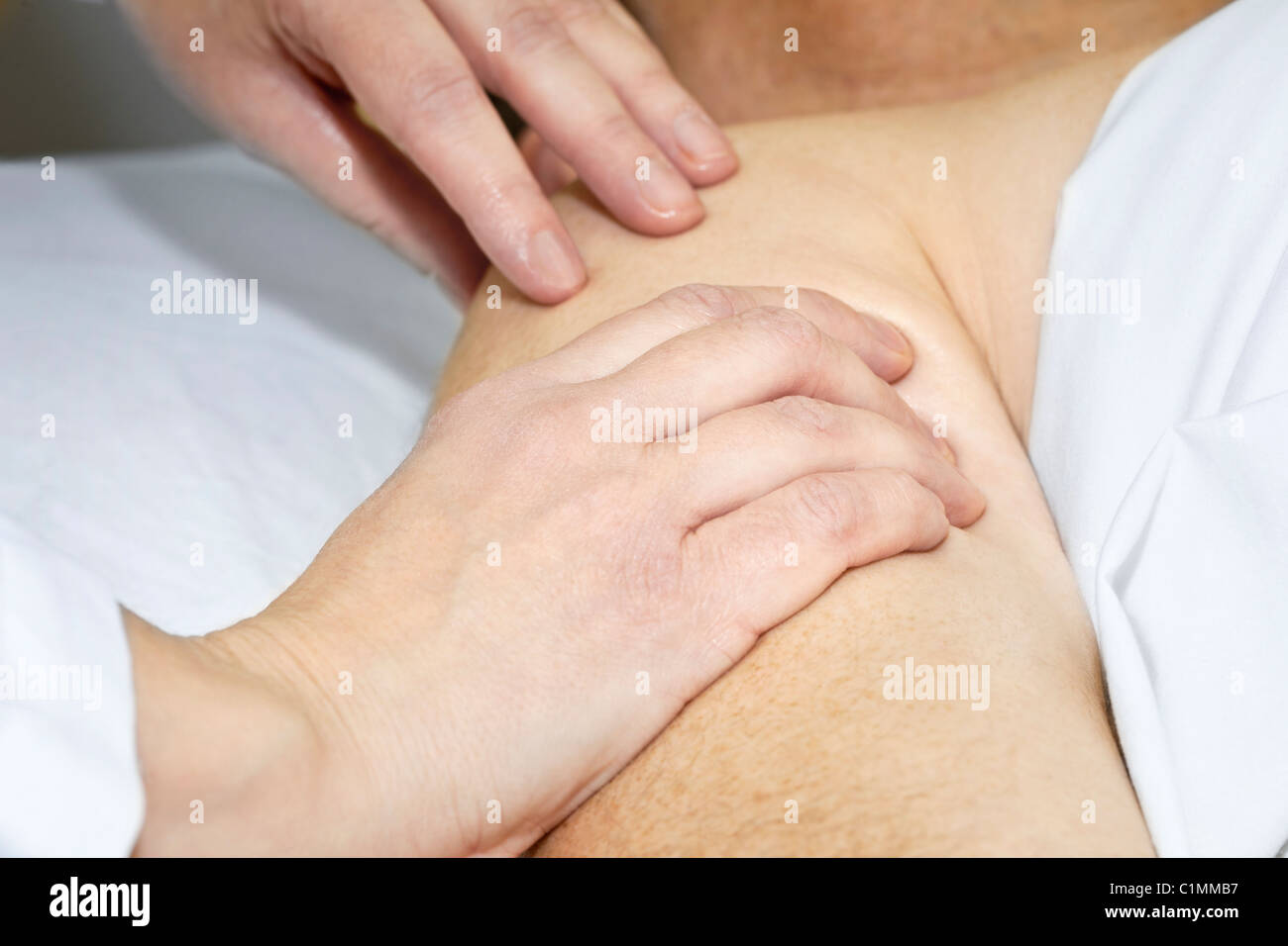 Closeup of female hands massaging arm and shoulder Stock Photo