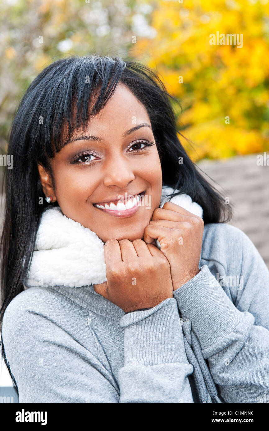 Portrait of happy smiling young black woman outside in the fall - Stock Image