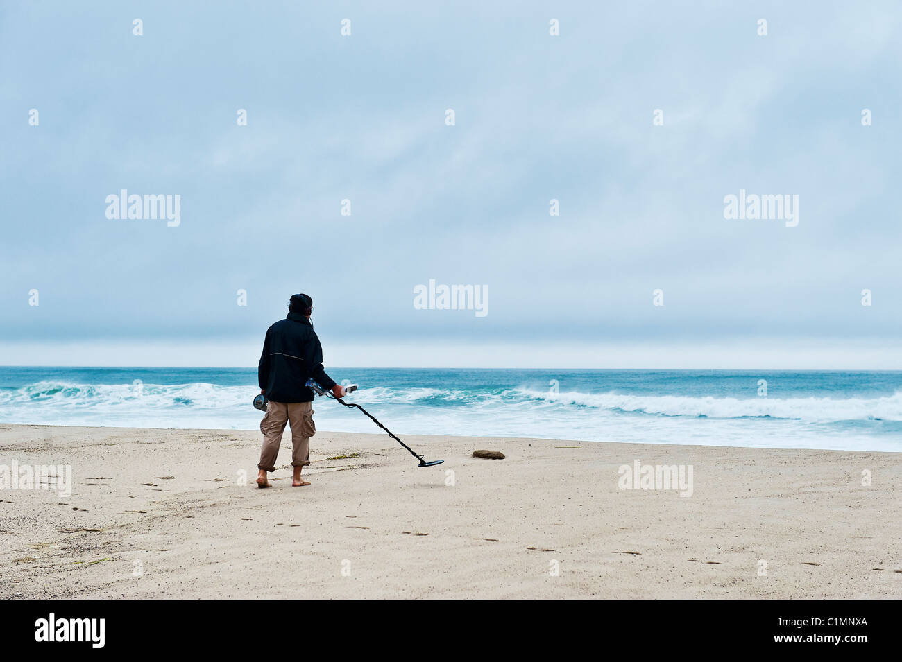 Man searching the beach with a metal detector. - Stock Image