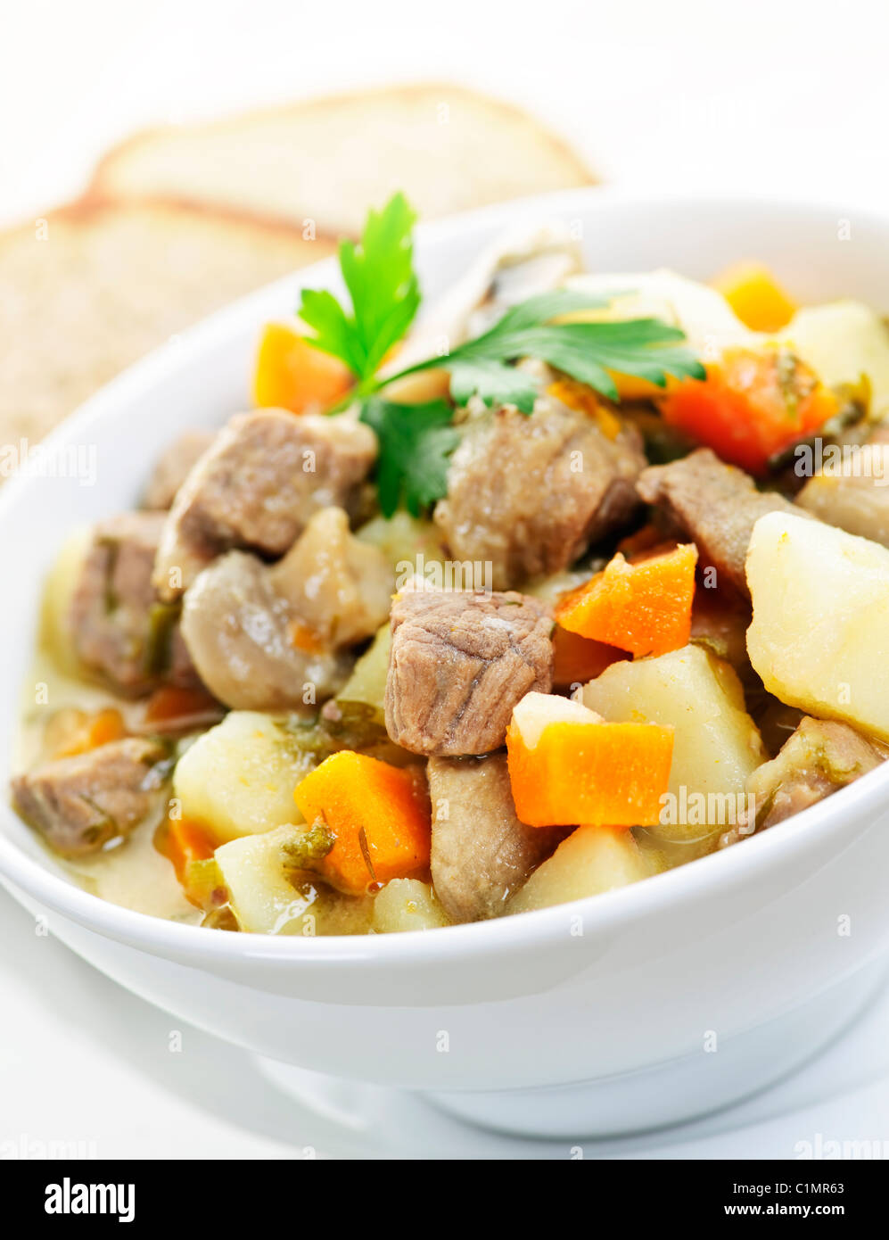 Bowl of hearty beef stew with vegetables served with rye bread - Stock Image