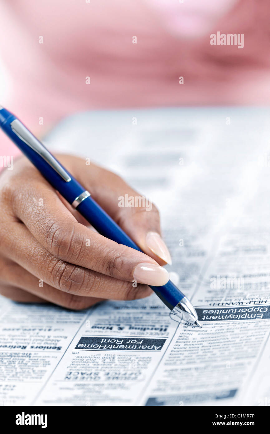 Black female hand circling ad in newspaper classified section looking for job - Stock Image
