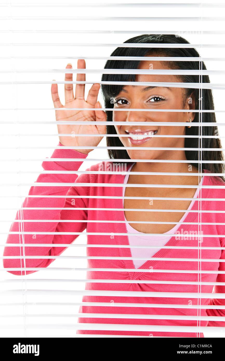 Happy young black woman looking through horizontal venetian blinds - Stock Image