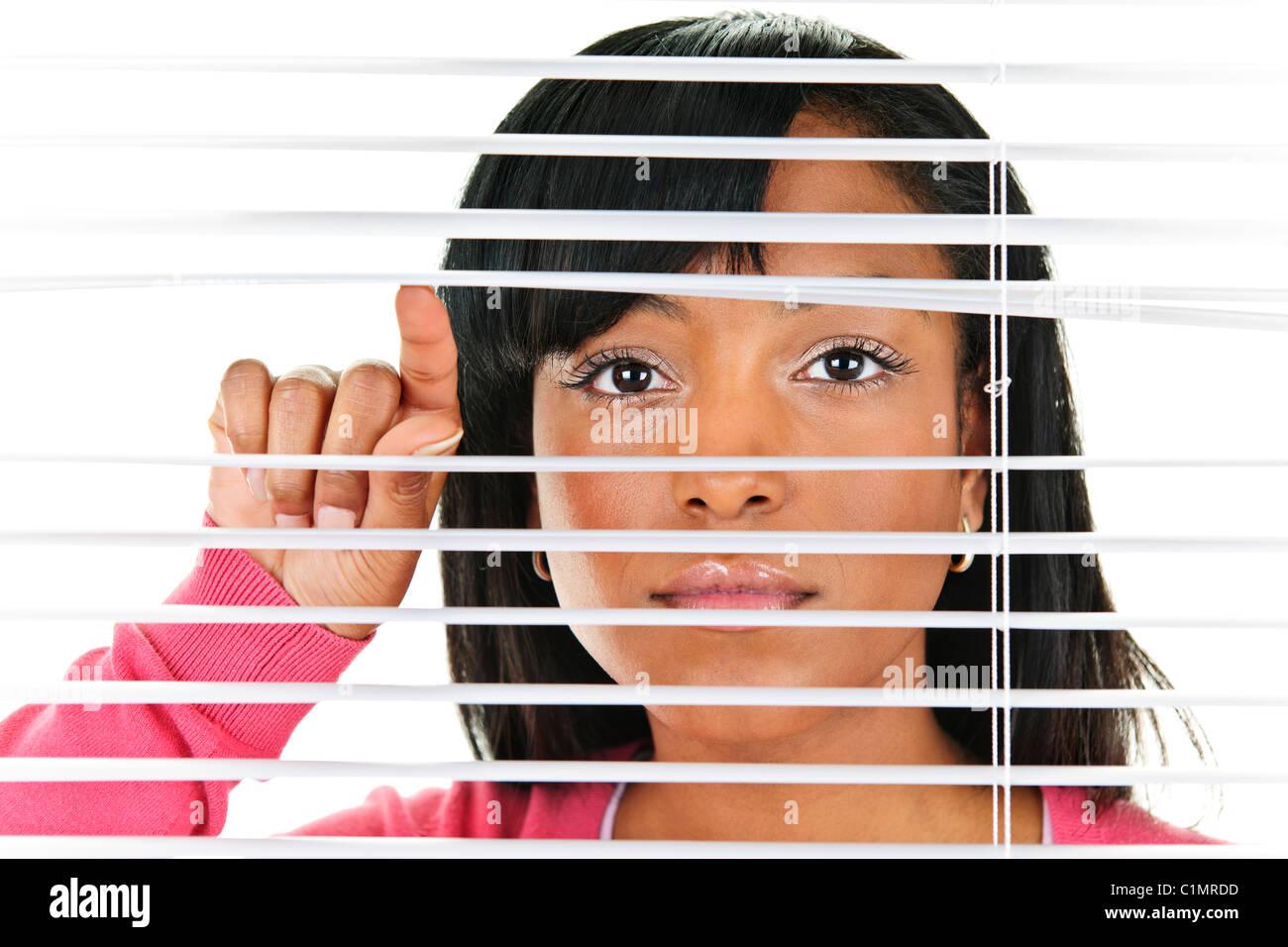 Young black woman looking through horizontal venetian blinds - Stock Image