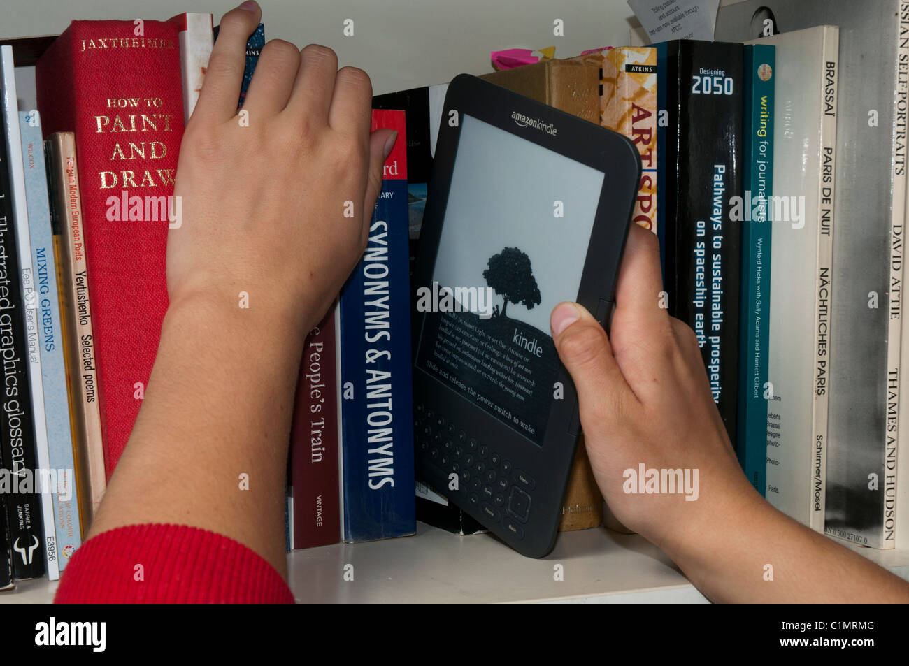 A Kindle 3 amongst traditional print books on a bookshelf - Stock Image