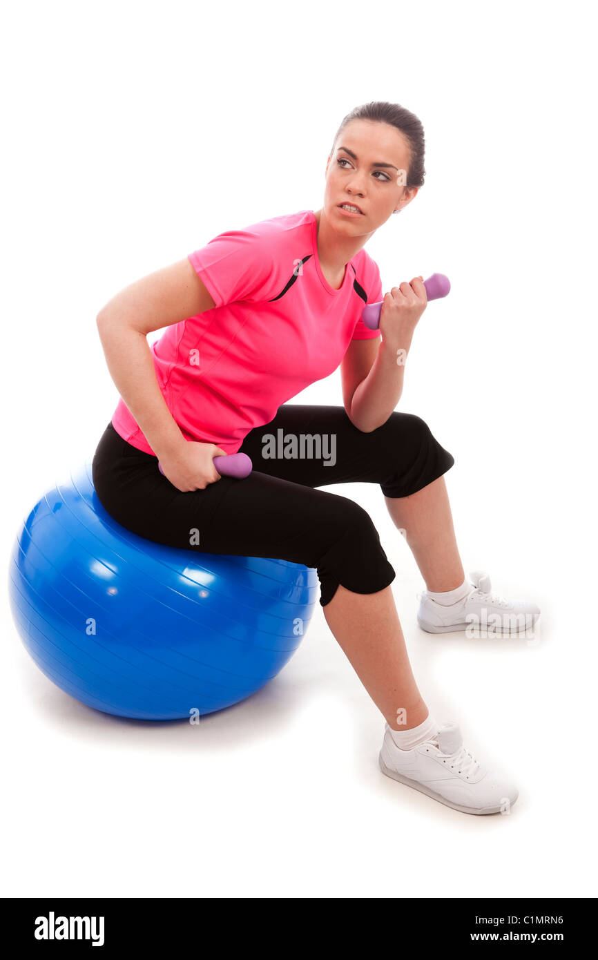 A young female lifting exercise weights sat a blue exercise ball - Stock Image