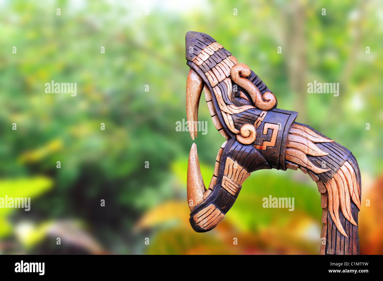 Chichen Itza Snake symbol wood handcraft figure in jungle Mexico Yucatan - Stock Image