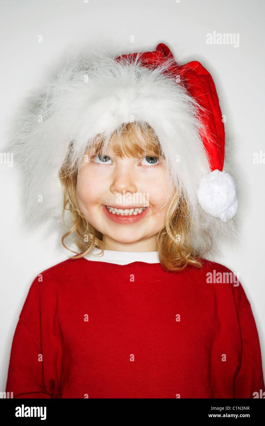 Girl wearing santa hat, looking up - Stock Image