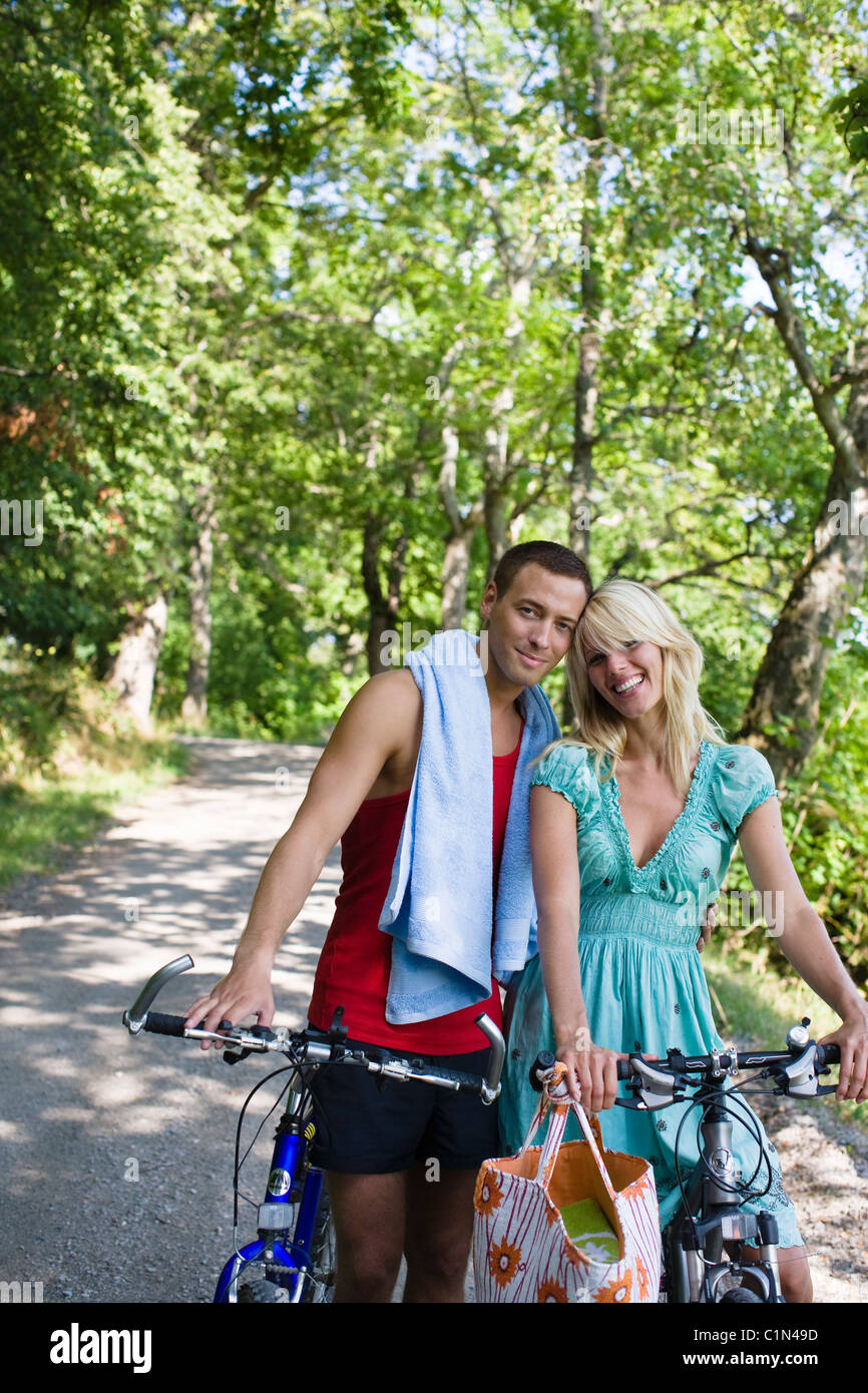 Portrait of young couple with bicycles in forest - Stock Image