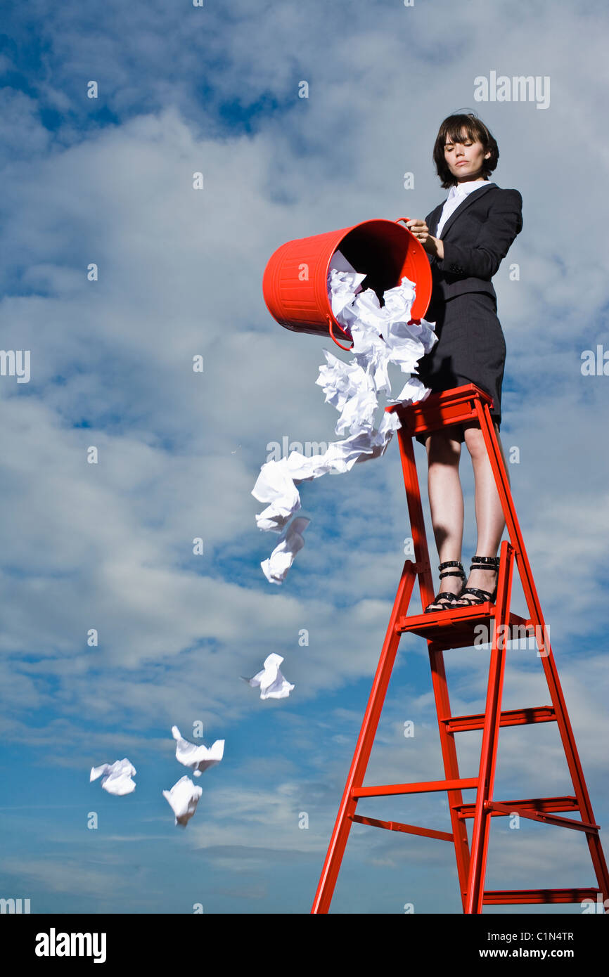 Woman throwing out rubbish from red bin standing on ladder - Stock Image