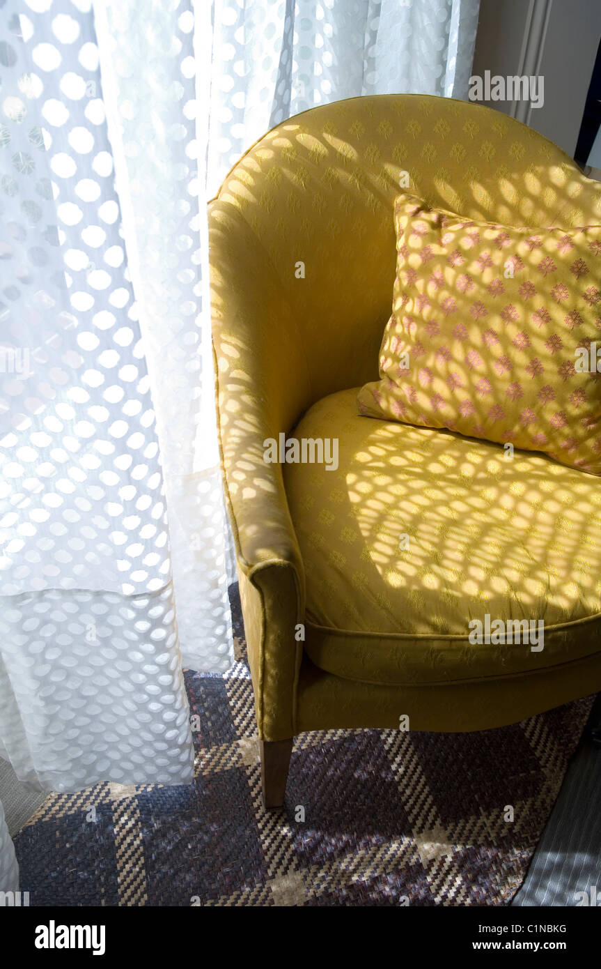 Yellow armchair by spotted net curtain on tartan style carpet - Stock Image