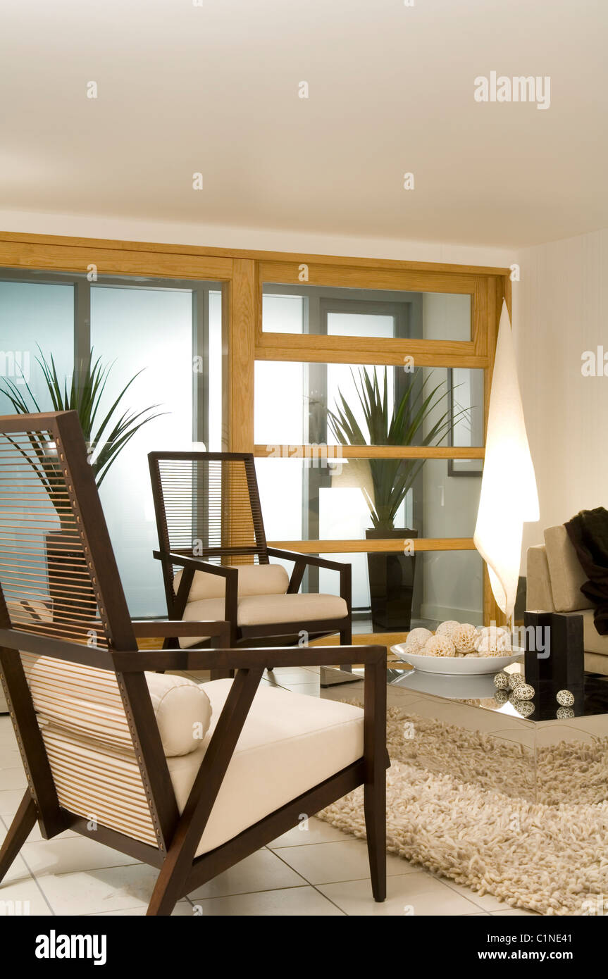 Wood framed armchairs in modern living room with shag pile carpet and panelled room screen - Stock Image
