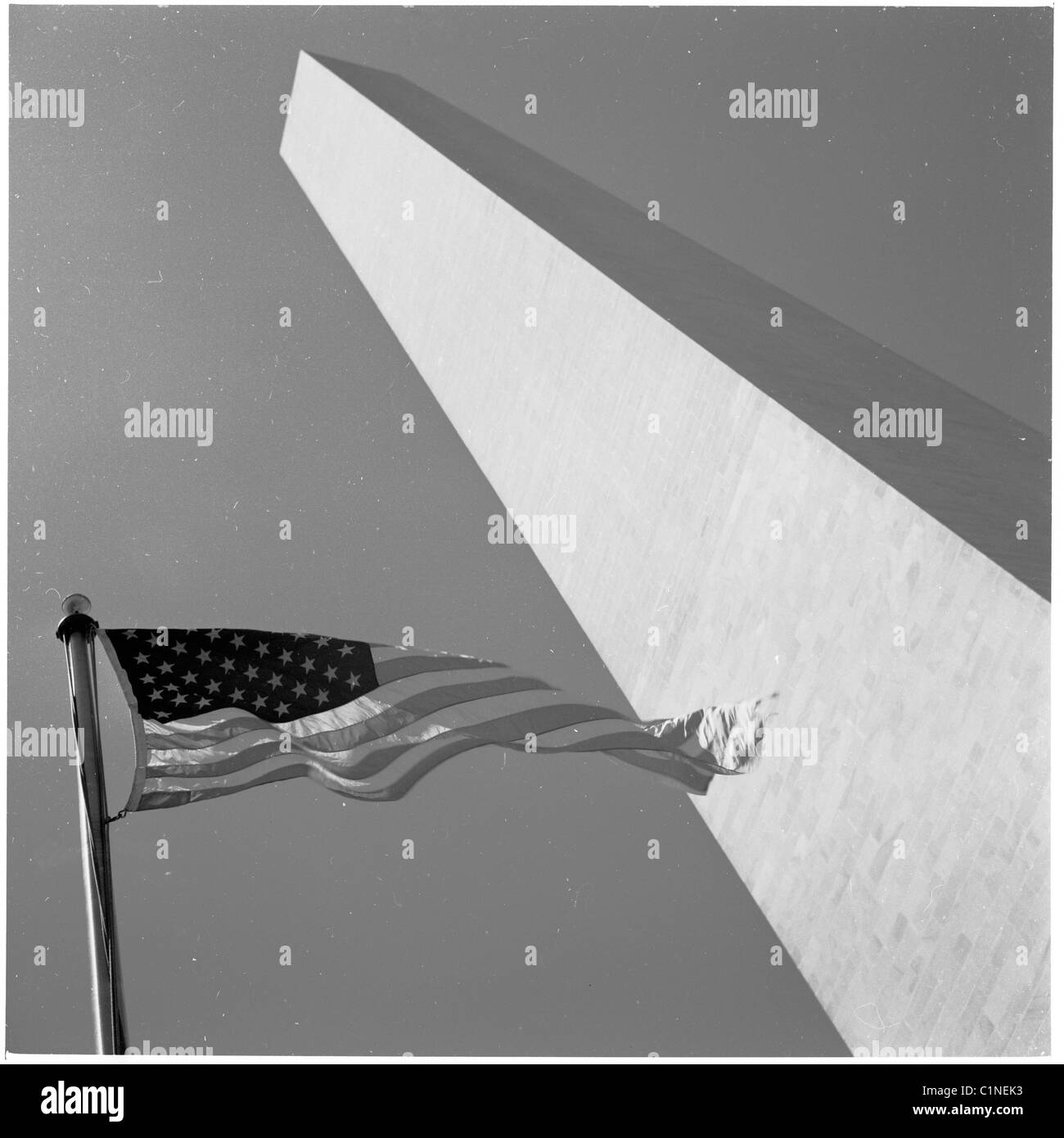 America, 1950s. Photograph by J Allan Cash. Exterior shot of the Washington Momument, with USA waving flag. - Stock Image