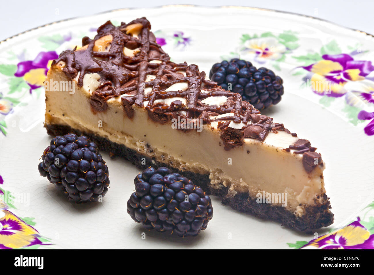slice of chocolate covered cheesecake on decorative plate - Stock Image