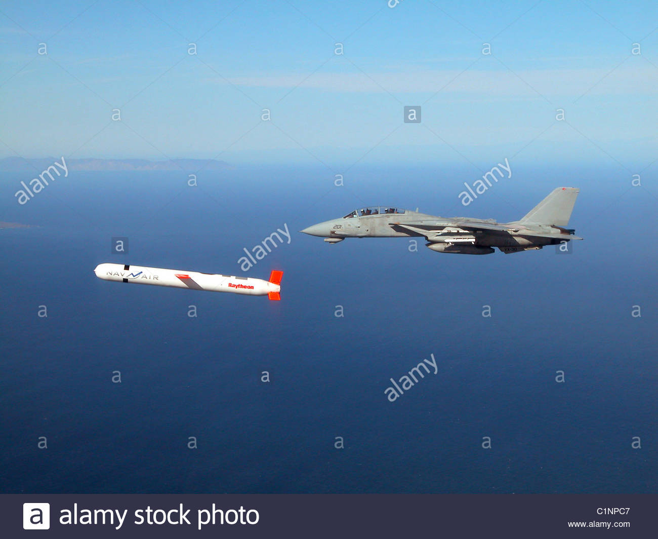 Tactical 'Tomahawk' Block IV cruise missile is escorted by a Navy F-14 'Tomcat' fighter - Stock Image