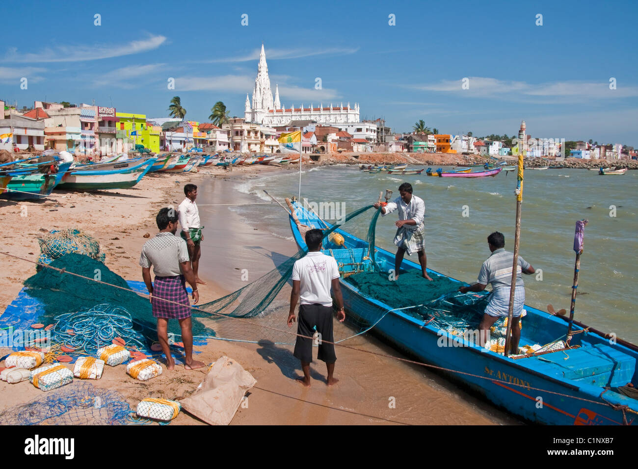 Fishermen on Kanyakumari Beach waterfront preparing nets with Our Lady of Ransom Church in background. - Stock Image