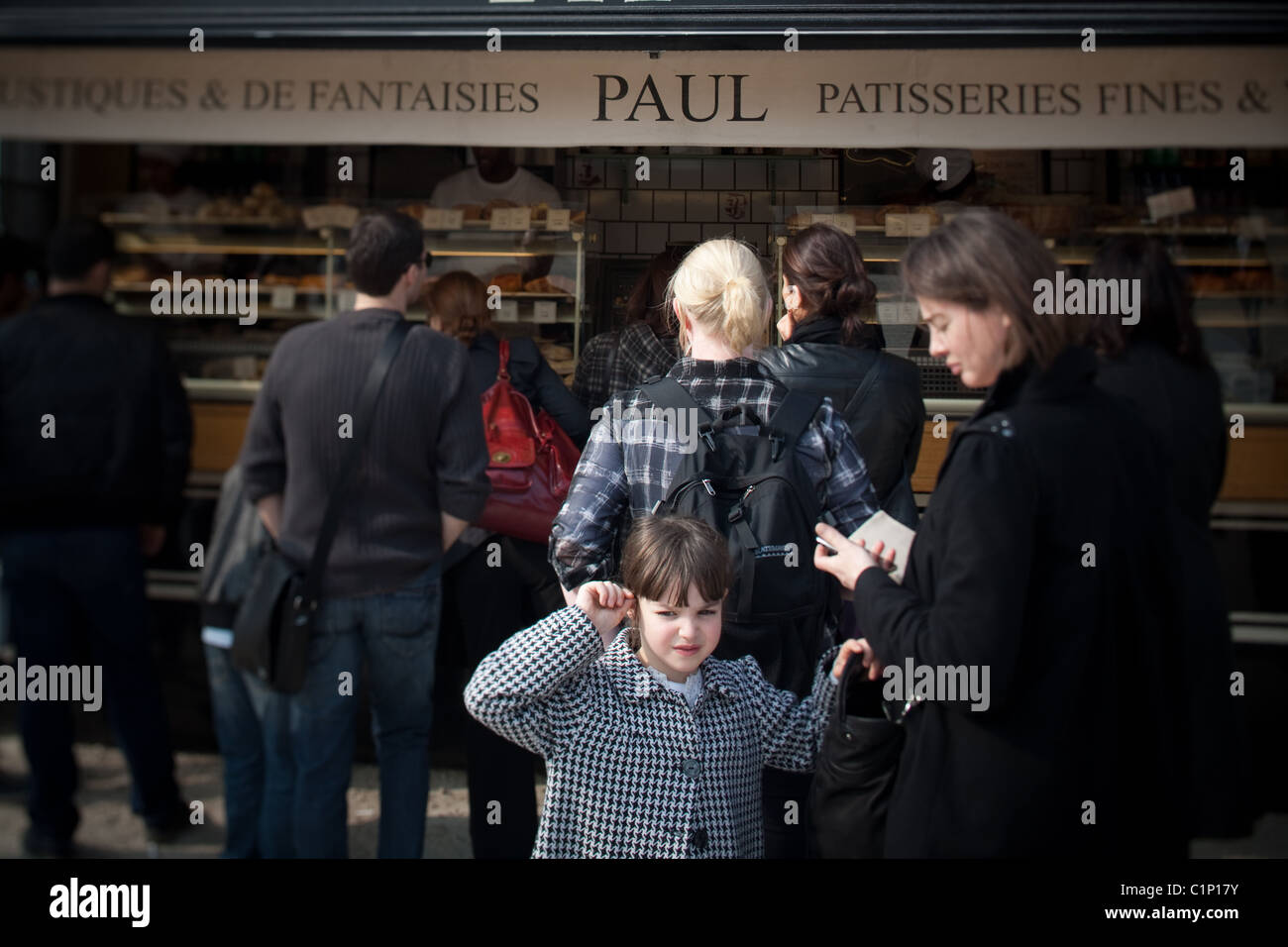 Mother and Daughter wait in line at an outdoor food vendor in Paris France. Paul Patisserie - Stock Image