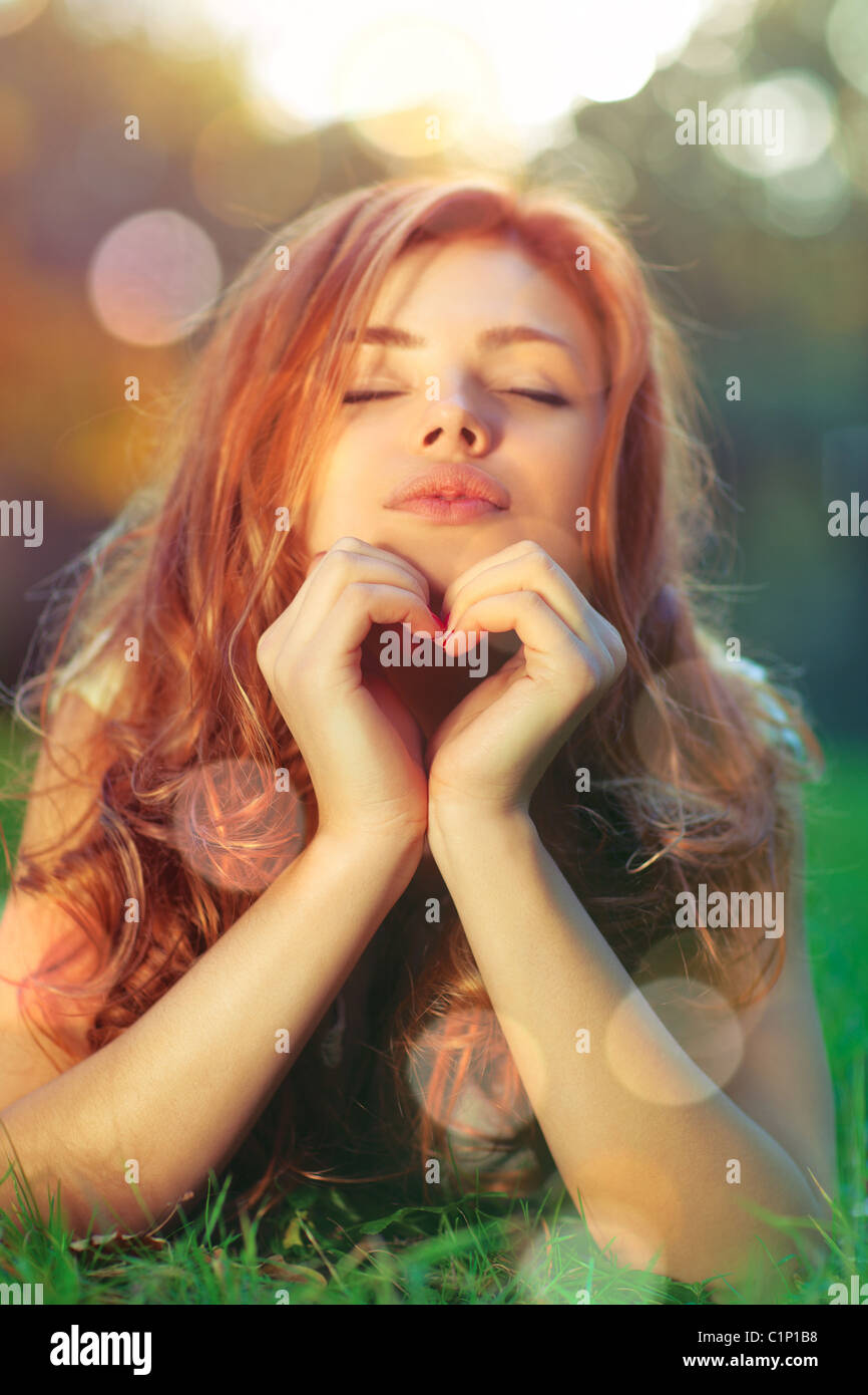 Young woman lying on grass and showing heart shape portrait. - Stock Image