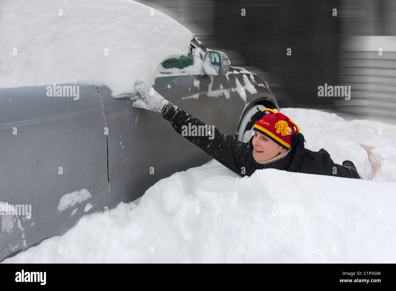 Young Woman Trying to Open A Car Door in Snowdrift - Stock Image