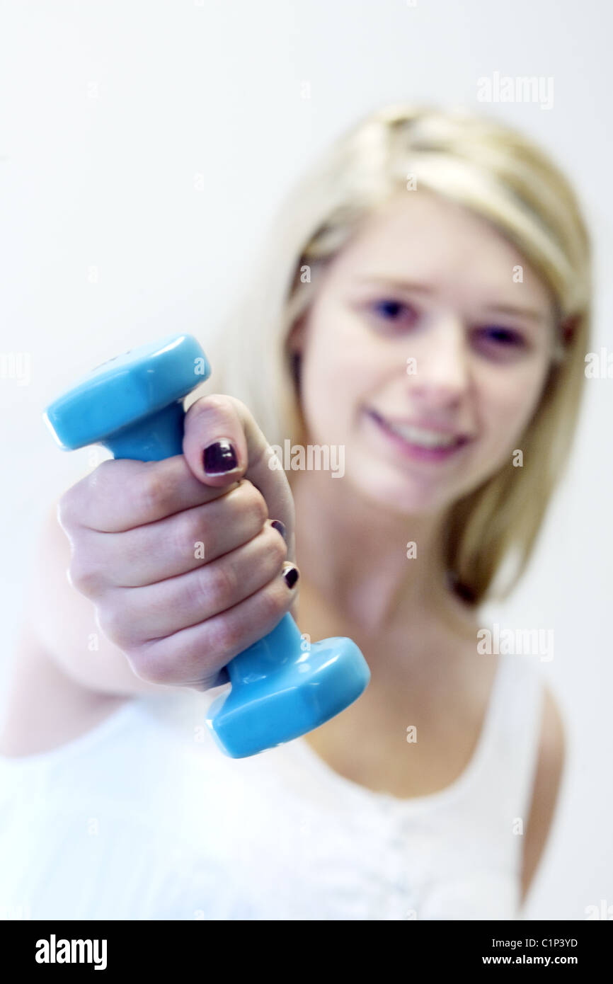 Blond teenage girl exercising with weights, UK - Stock Image