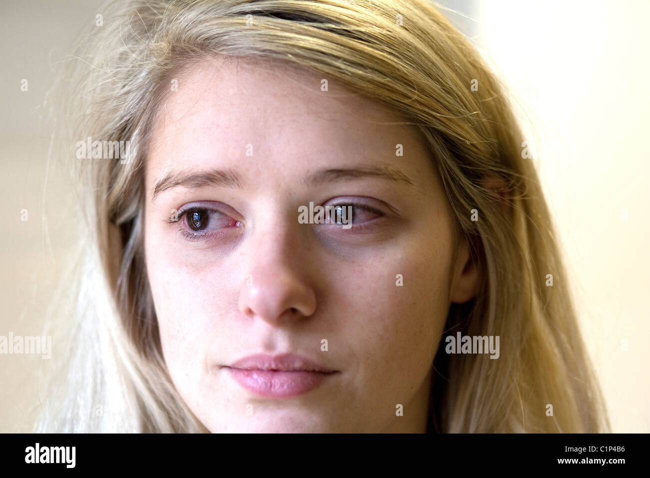 Tearful blond teenage girl, close up of face - Stock Image