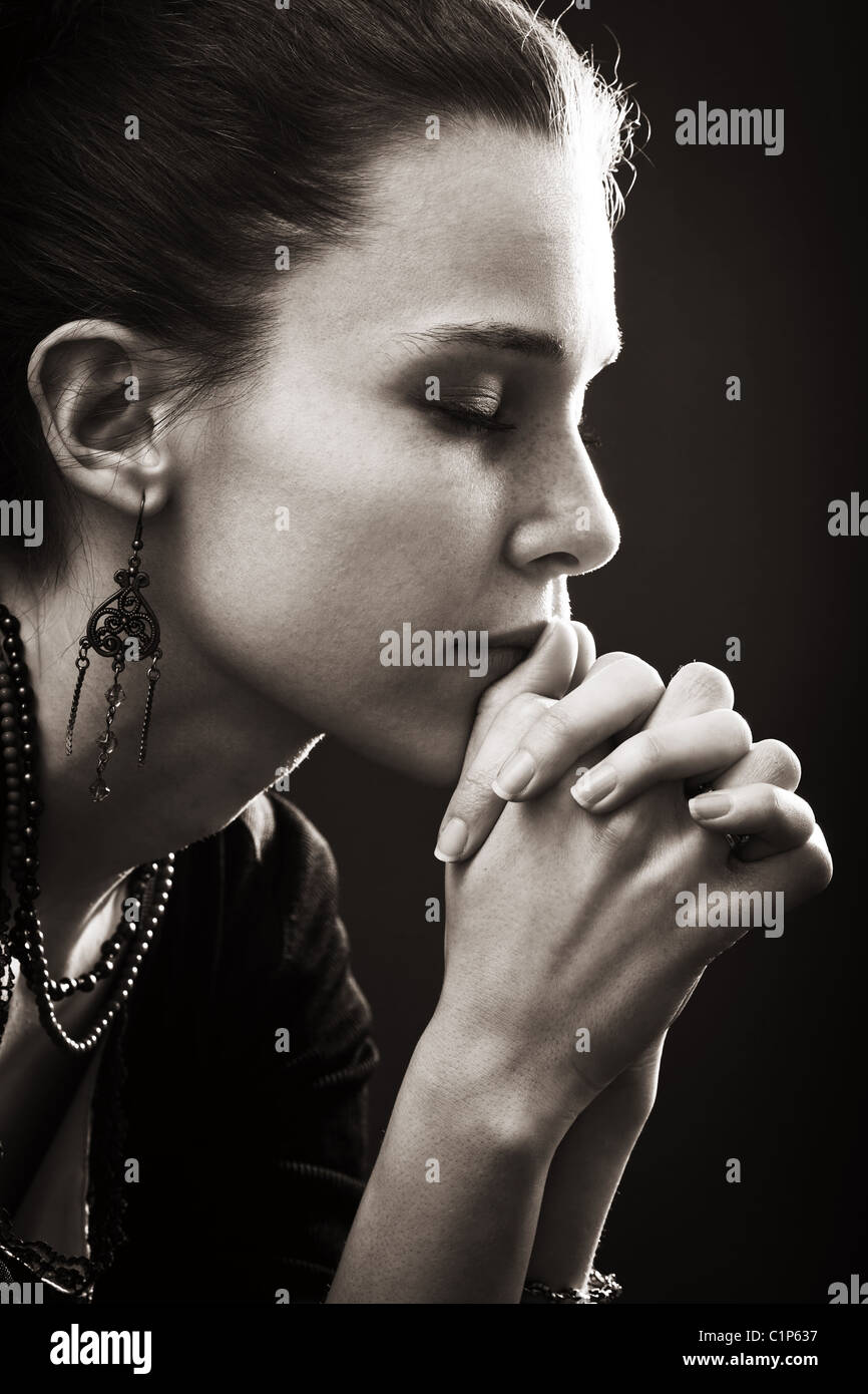 Faith and religion - spiritual woman praying in darkness - Stock Image
