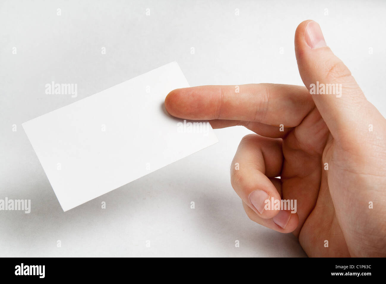 Hand holding blank business card over white - Stock Image