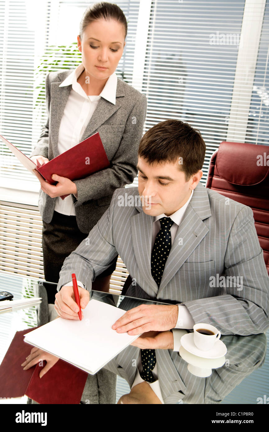 Portrait of serious boss going to sign contract while executive secretary standing near by - Stock Image