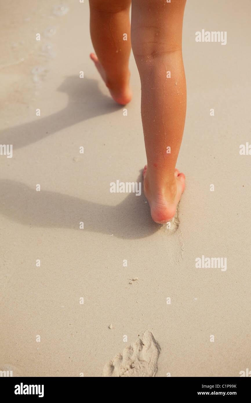 Low section of girl walking on sand leaving footprints - Stock Image